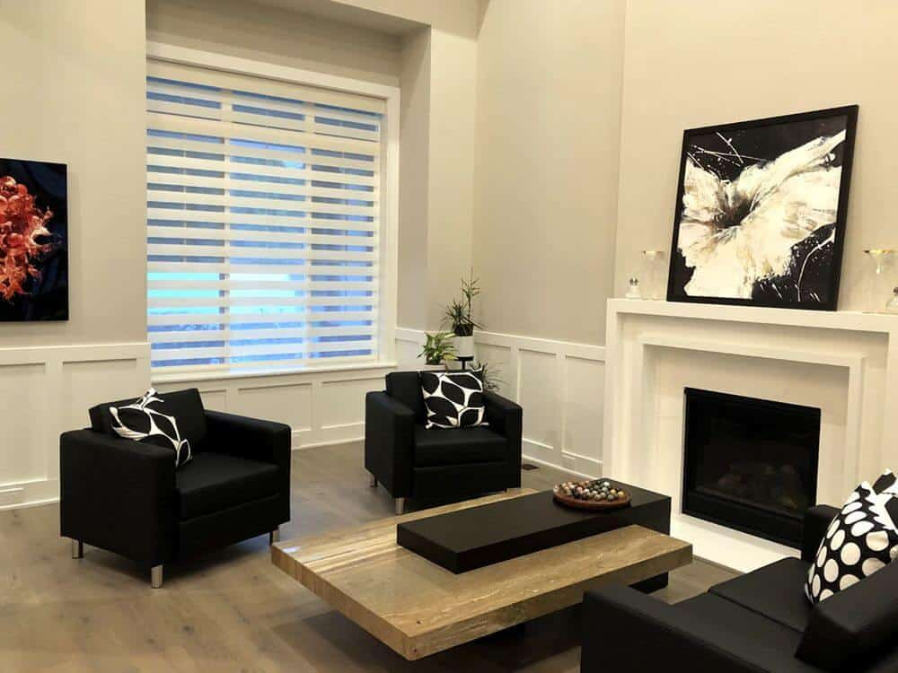 This living room boasts a modern sofa set and a stylish center table, along with a fireplace and hardwood flooring. There's a window as well featuring a transitional window shade.