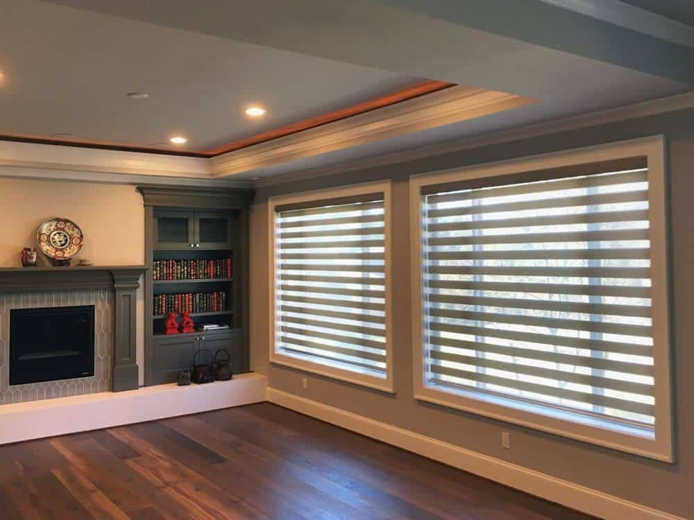 A spacious living space featuring gray walls and a striking tray ceiling, along with hardwood flooring. The area features built-in shelving and a fireplace. There are large windows as well with transitional window shades.