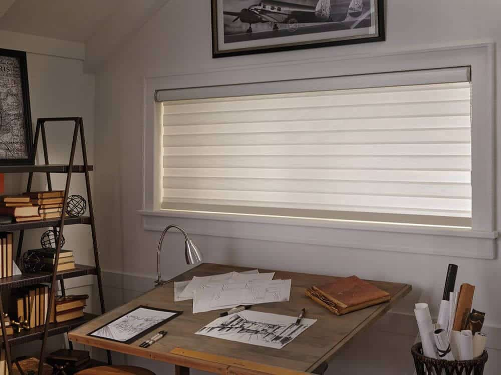 A home office featuring a square drafting table set near the window featuring a transitional window shade. There's a freestanding shelf on the side as well.