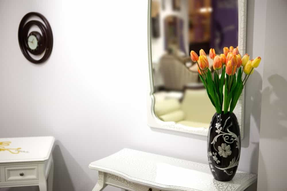 Tulips on a black vase placed on top of a dresser.