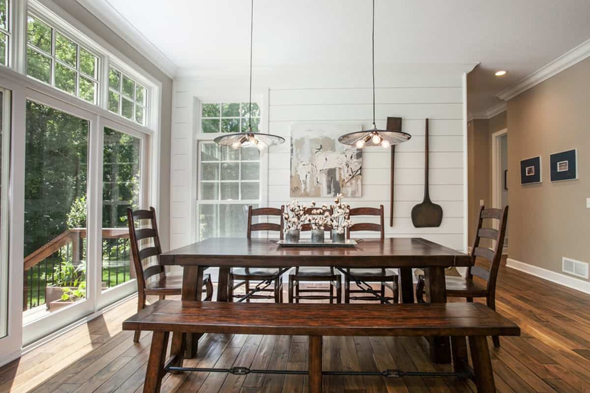 This is a charming and homey dining area with a simple dark wooden dining table paired with a long wooden bench and wooden chairs. These match well with the hardwood flooring and the wall-mounted decorations on the white wall.