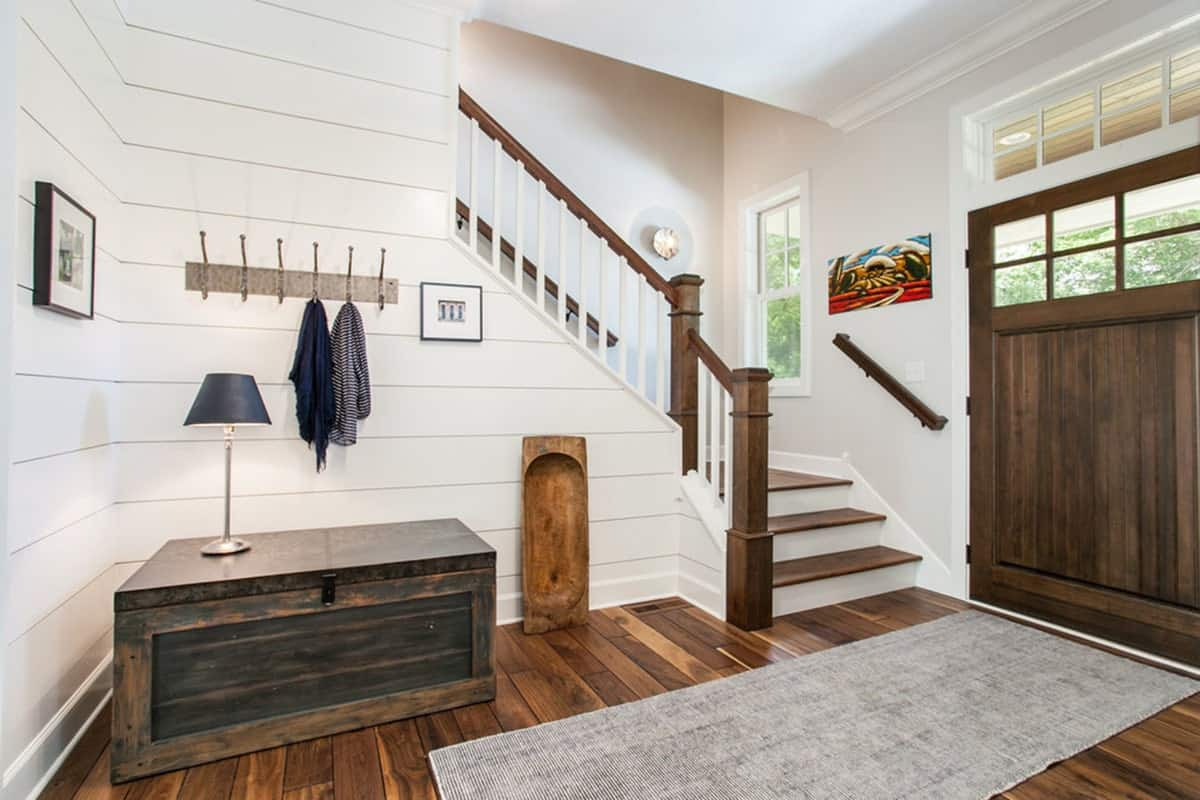 This is a charming foyer with a wooden main door that matches with the hardwood flooring topped with a gray area rug. On the side of the wooden staircase is a waist-high wooden drawer that bears a table lamps topped with a wall-mounted coat and hat rack.
