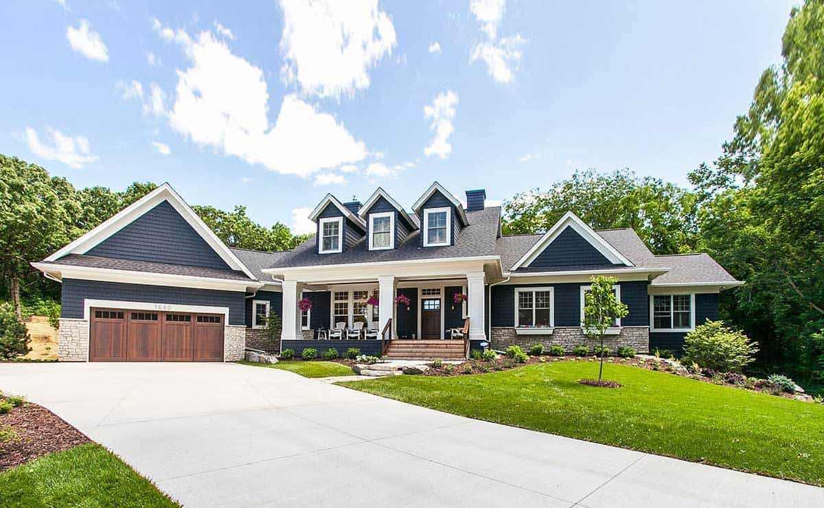The front of the beautiful house has a large concrete driveway leading to the dark brown garage doors. From it, a small walkway diverges that leads to the main entry landscaped with grass and shrubs.