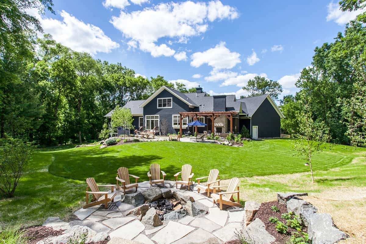 The back of the house has a large lawn of grass leading to a wonderful sitting area around a rustic stone firepit.
