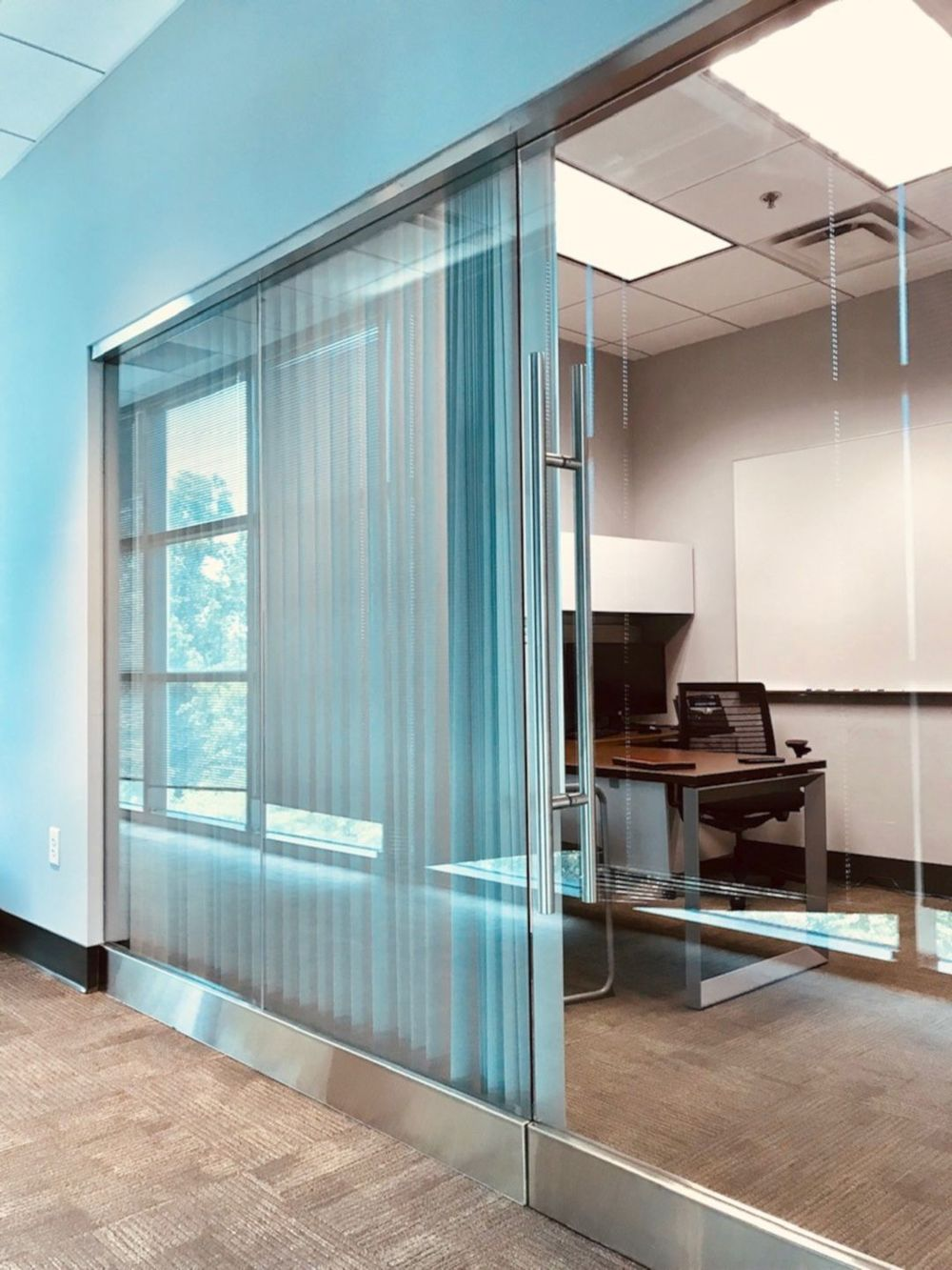An office room with a glass wall and door. It also has carpeted flooring and tiled ceiling.