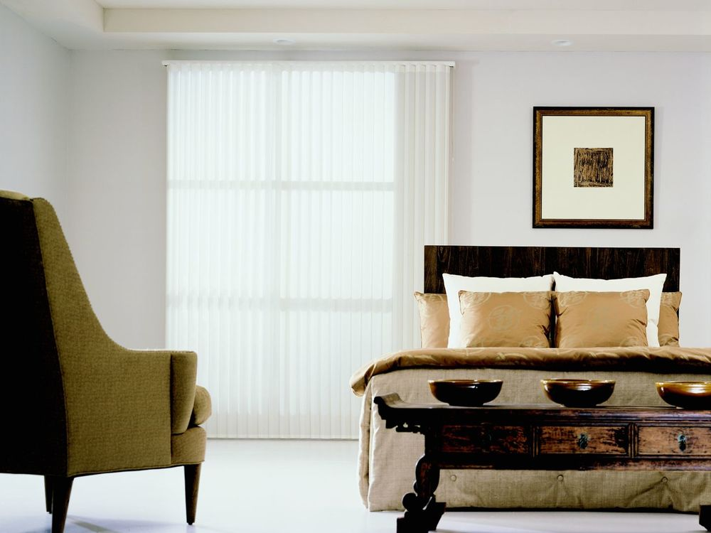 This primary bedroom offers an elegant bed set along with classy table and a gorgeous chair. The room has white walls, white flooring and a white tray ceiling.