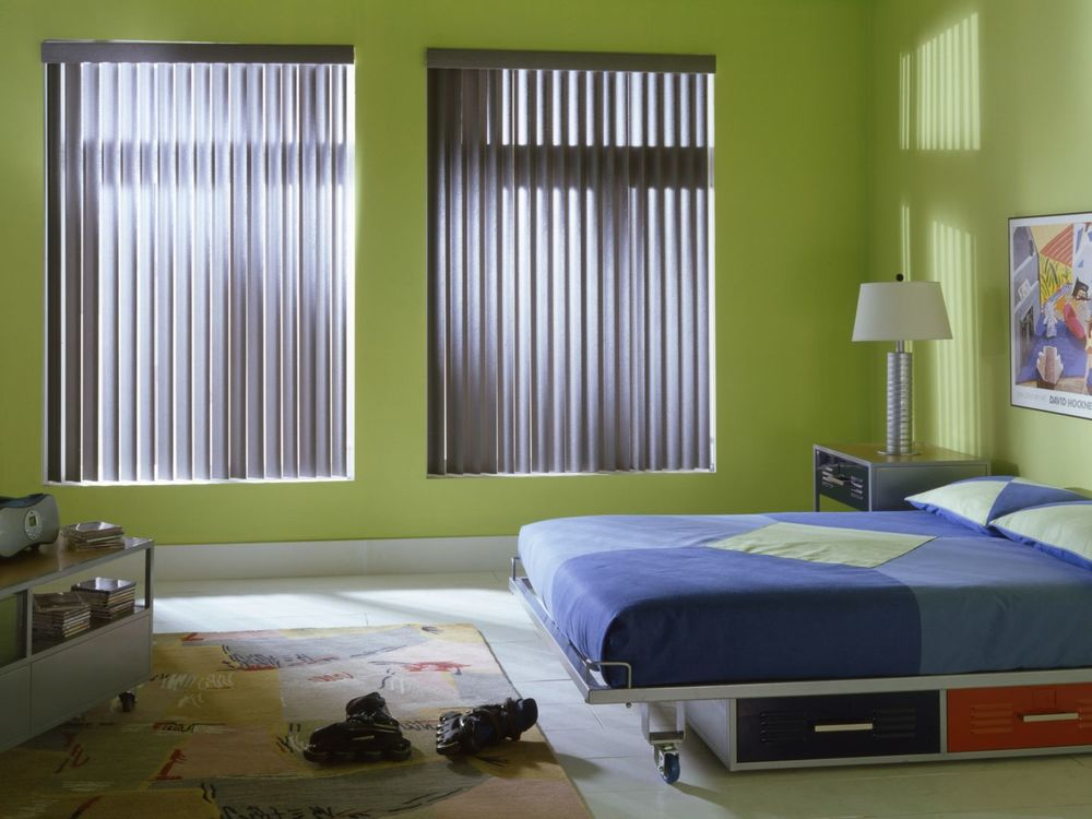 A boys' bedroom with green walls and large windows with vertical window blinds. It also has tiles flooring topped by an area rug.
