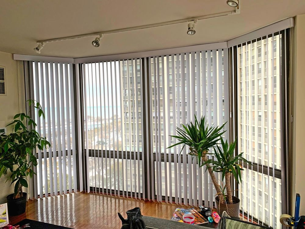 A close up look at this study desk's glass windows covered by vertical window blinds. It is also lighted by track ceiling lights.