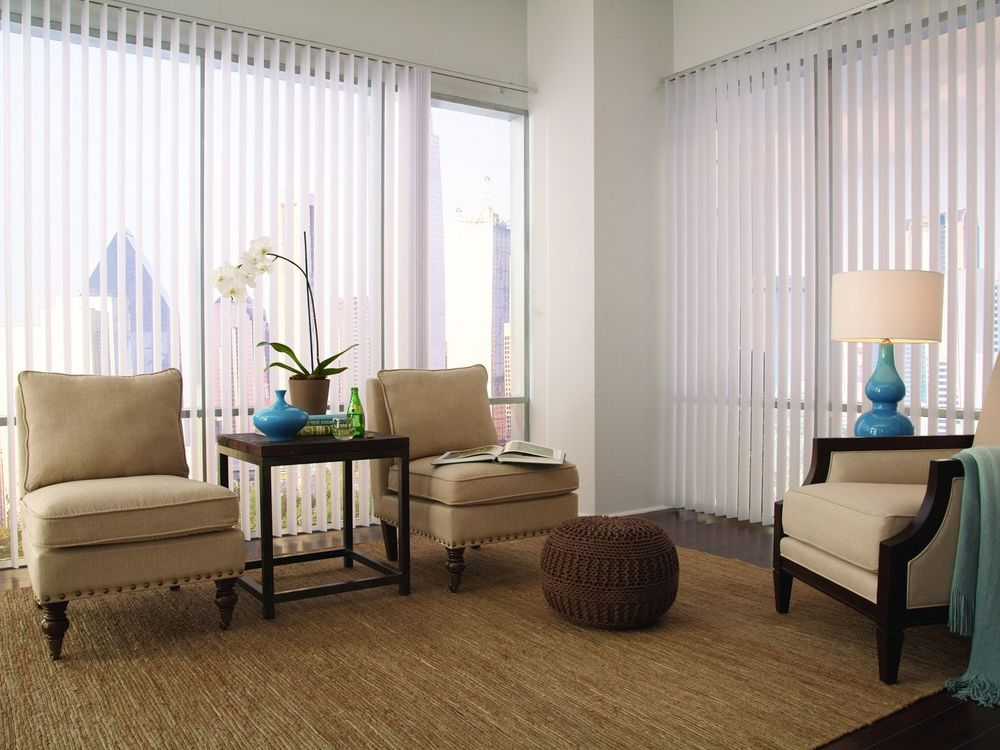 A living space featuring a pair of charming brown chairs and a center table on top of a brown area rug covering the hardwood flooring. The home's windows' feature white vertical blinds.