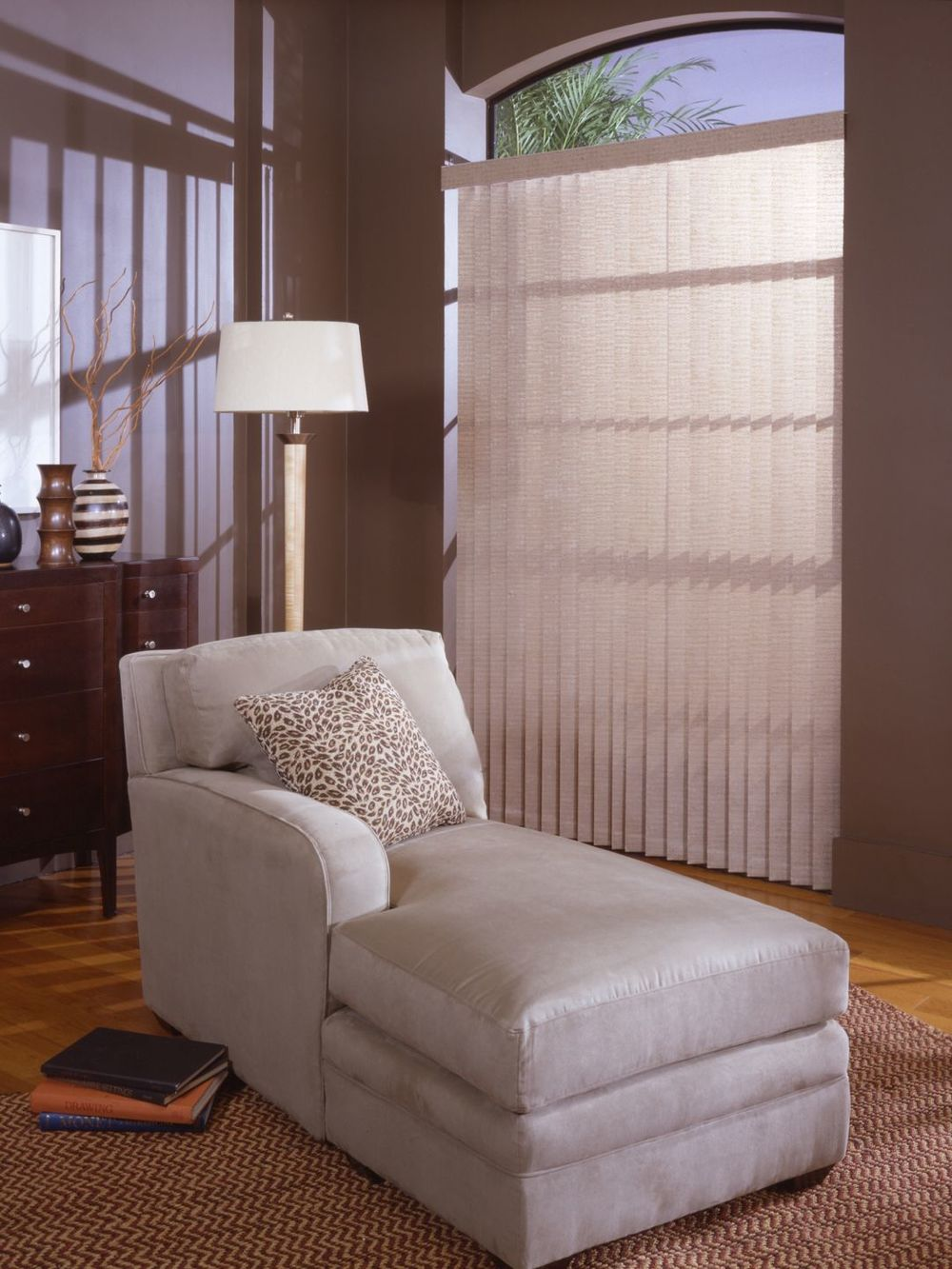 A focused look at this home's comfy chair on top of a brown area rug covering the hardwood flooring. The window is covered by a vertical window blinds as well.