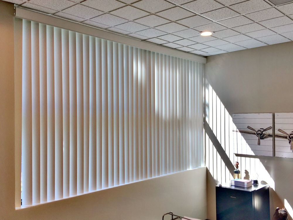 A focused look at this home's large top window with large vertical window blinds.