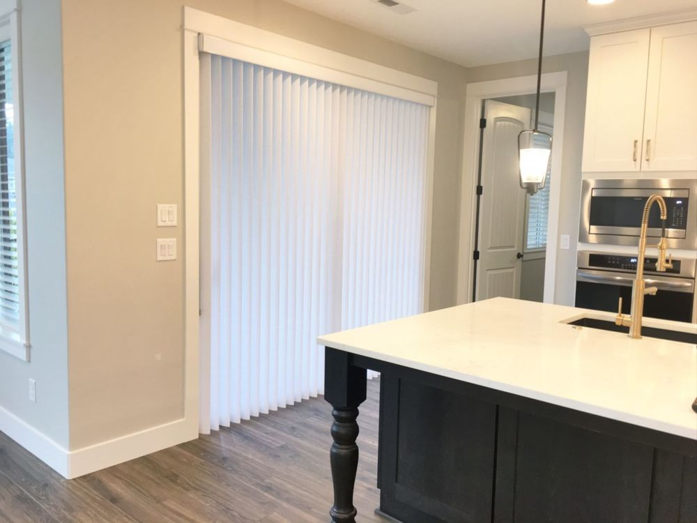 This kitchen features light gray walls and hardwood floors, it also offers a large center island with a white countertop and has large windows with vertical window blinds.