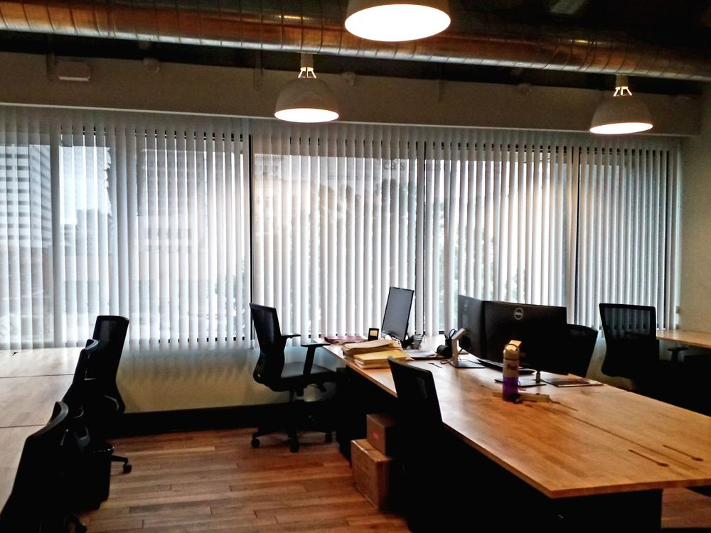 A large office area boasting hardwood flooring and multiple pendant lights. There are multiple wood-top working table and modern black chairs, along with windows featuring vertical window blinds.