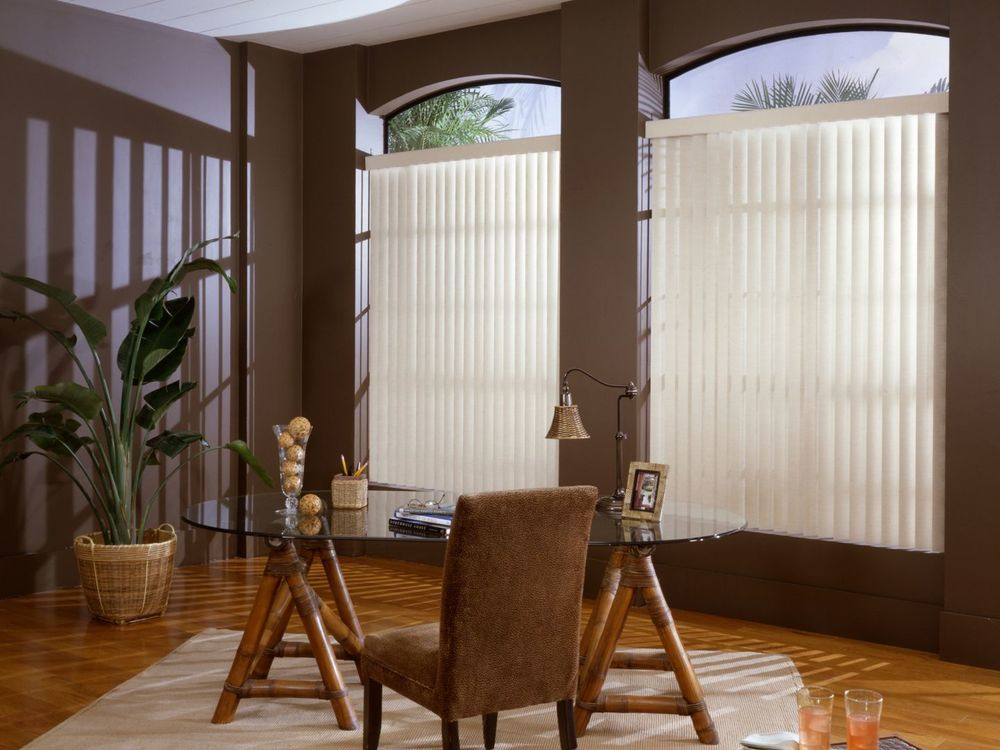 A focused look at this home's magnificent office area with brown walls and hardwood floors. It offers a stylish glass top table with a brown chair on top of an area rug. The windows are covered by white window blinds.