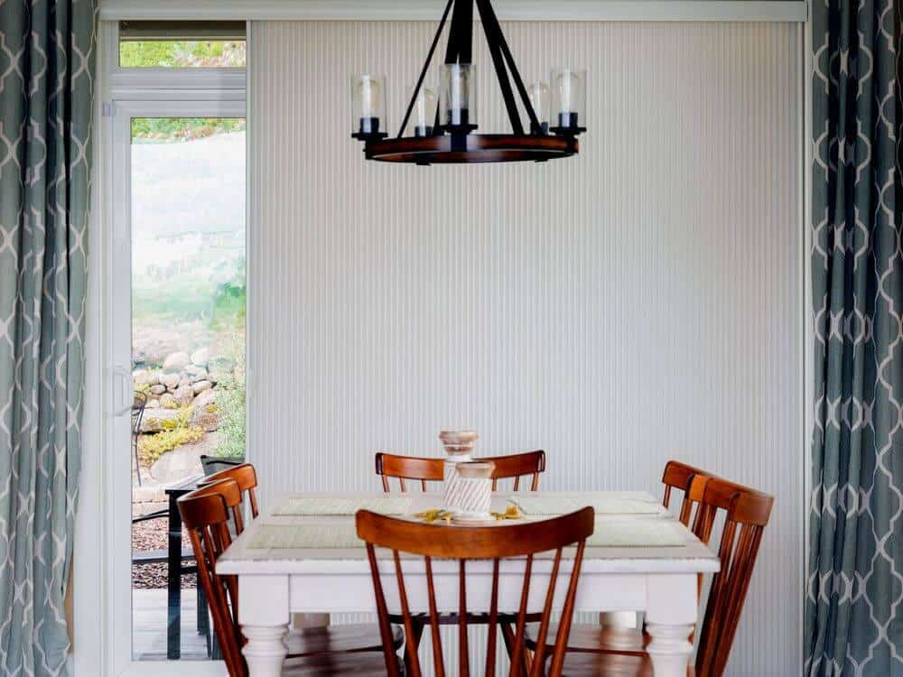A focused look at this home's classy dining table and chairs setup lighted by a gorgeous ceiling light. The window is covered by a vertical cellular window shade.