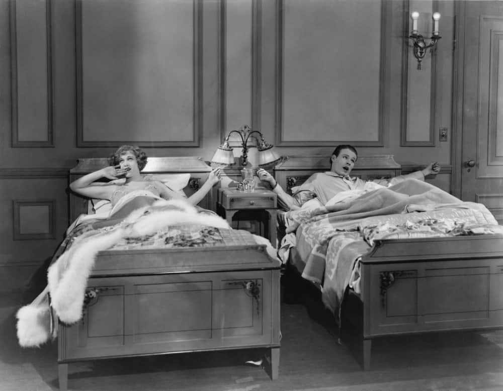 Vintage image of a couple in twin beds.
