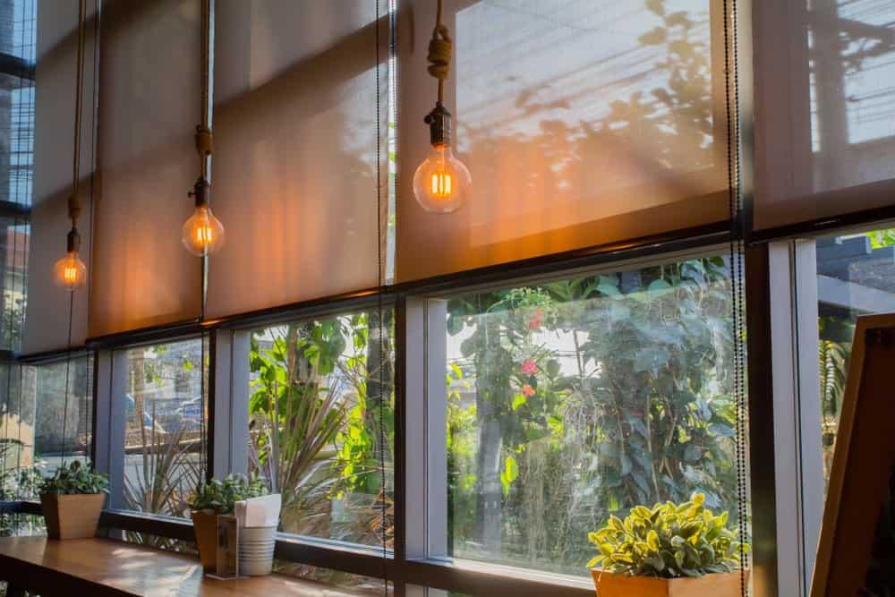 Black framed windows covered in translucent roller shades.