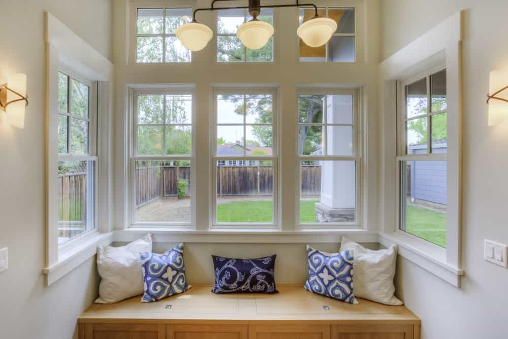 White framed windows above a wooden seat nook.