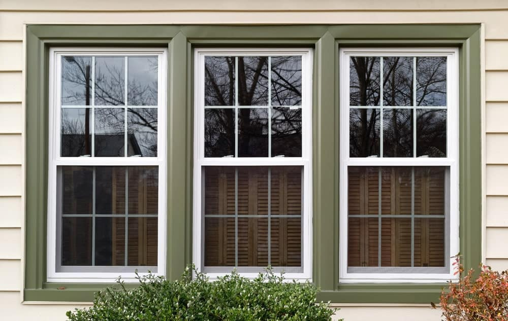 Three-panel windows in moss green frames.