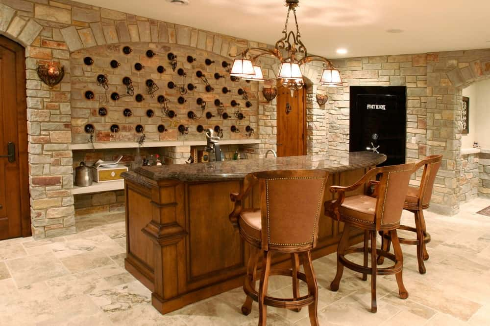 A luxurious-looking cellar with stone walls and tiles flooring. It offers a large counter with a bar lighted by a glamorous chandelier.