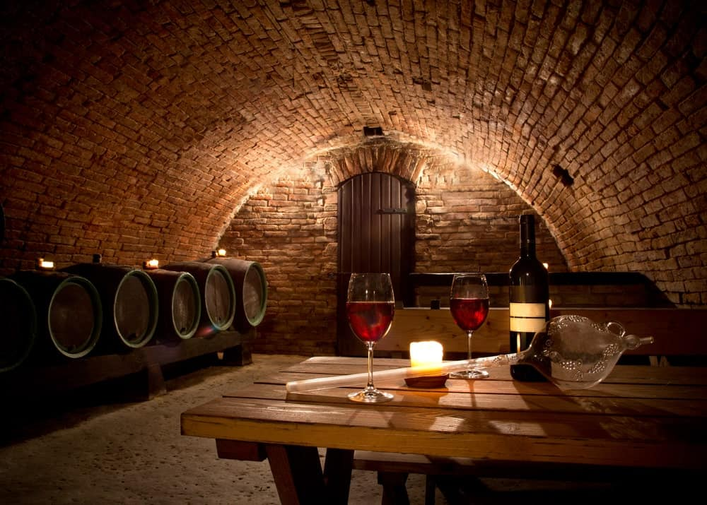 A large underground wine cellar featuring a wooden table and chairs set and has brick walls and ceiling.