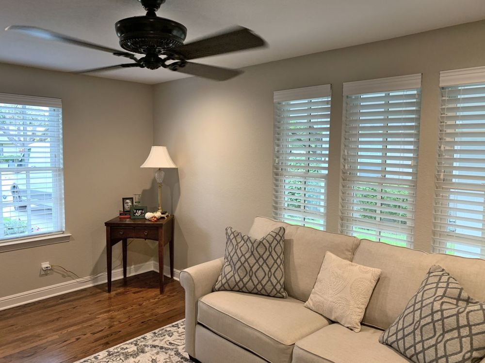 A closer look at this living room's sofa and windows featuring window blinds. The room has gray walls and hardwood floors.