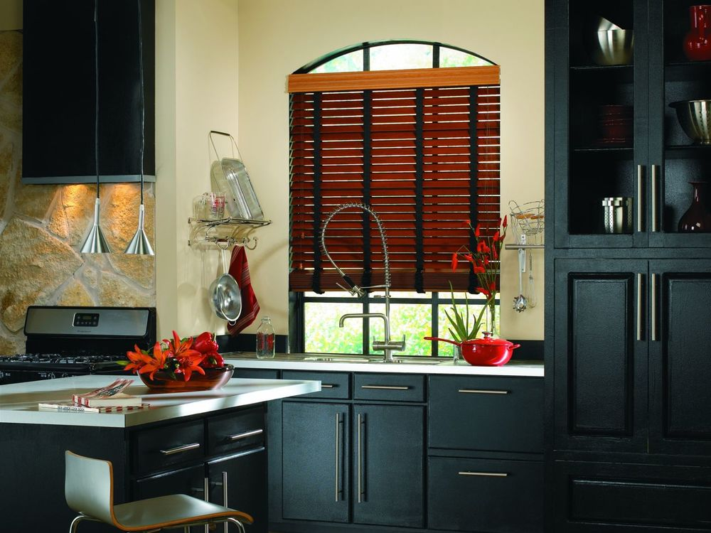 A stylish wooden blinds installed in a kitchen window, where the kitchen sink counter is set.