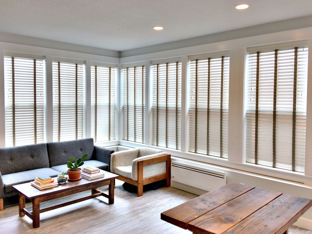 Composite wood blinds on the surrounding windows of a small white living room.