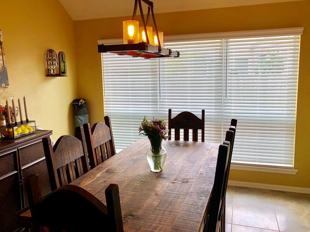 A dining room featuring a classy wooden dining table set paired with wooden chairs, surrounded by yellow walls and a vaulted ceiling. The windows also feature window blinds.
