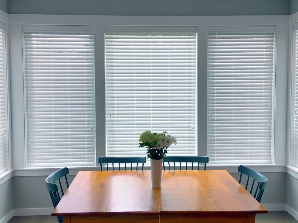 A focused look at this small dining room's dining table set surrounded by gray walls and windows featuring window blinds.