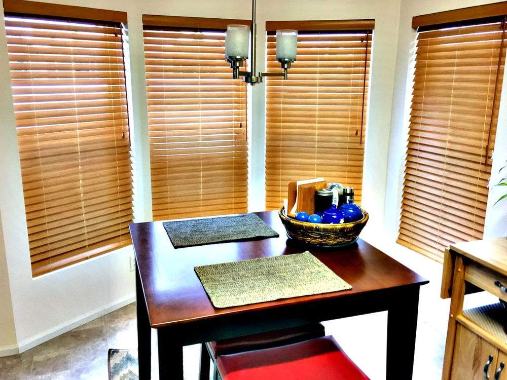 A closer look at this kitchen's square breakfast nook lighted by a charming ceiling light and is surrounded by wooden window blinds.