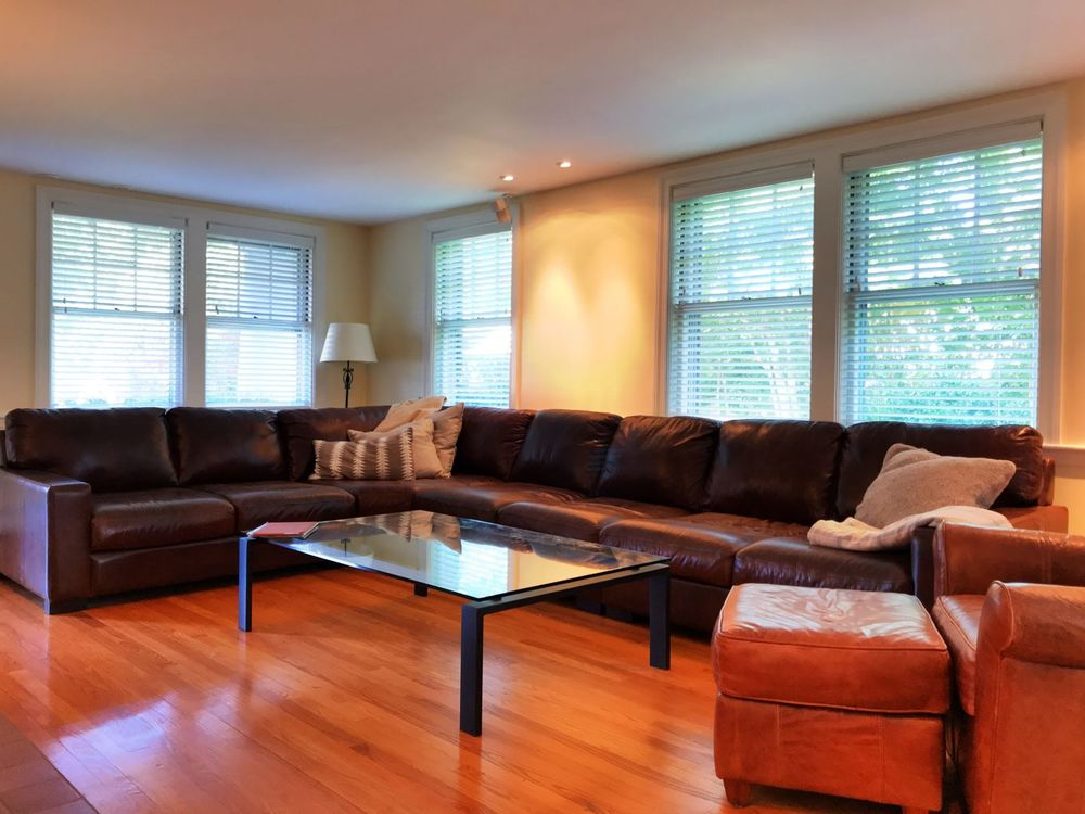 A living space boasting a massive leather L-shaped sofa set along with a glass top center table. The area features beige walls and hardwood floors, along with windows featuring blinds.