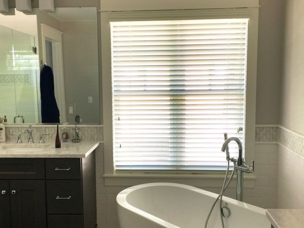 This primary bathroom offers a walk-in shower, a sink counter and a freestanding tub set by the window.