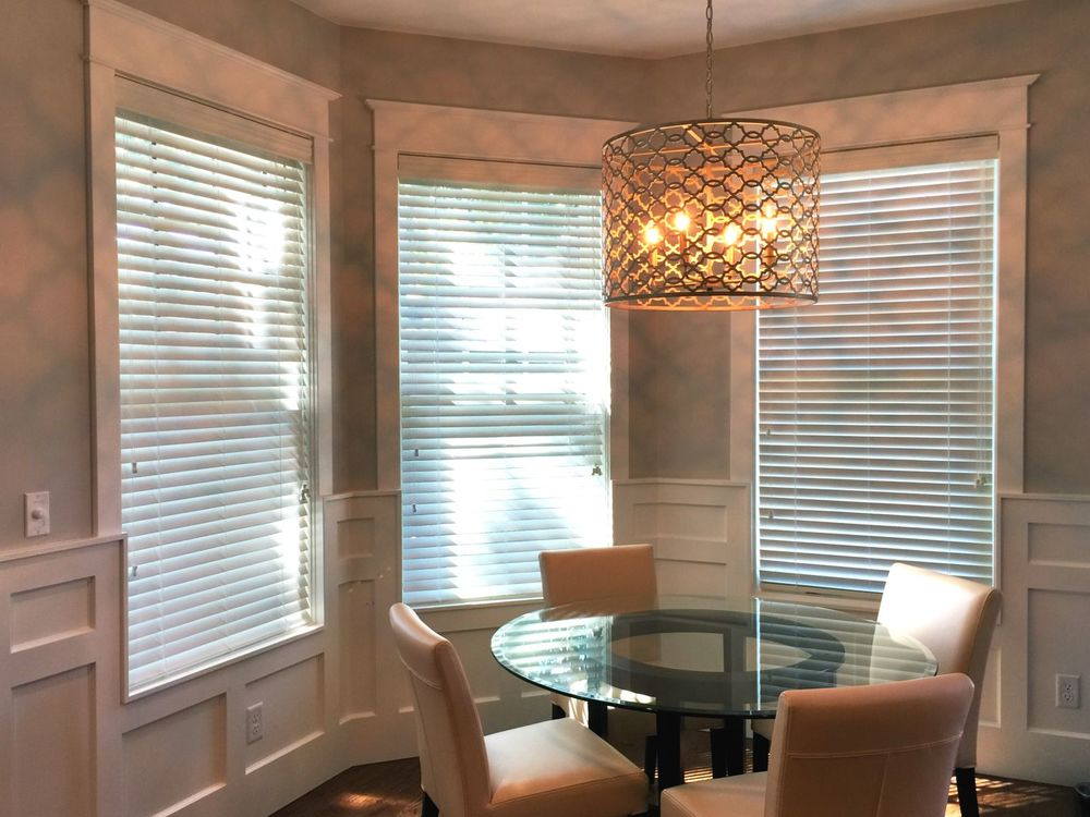 This dining nook offers a glass top round dining table lighted by a gorgeous ceiling light and is surrounded by windows covered by window blinds.