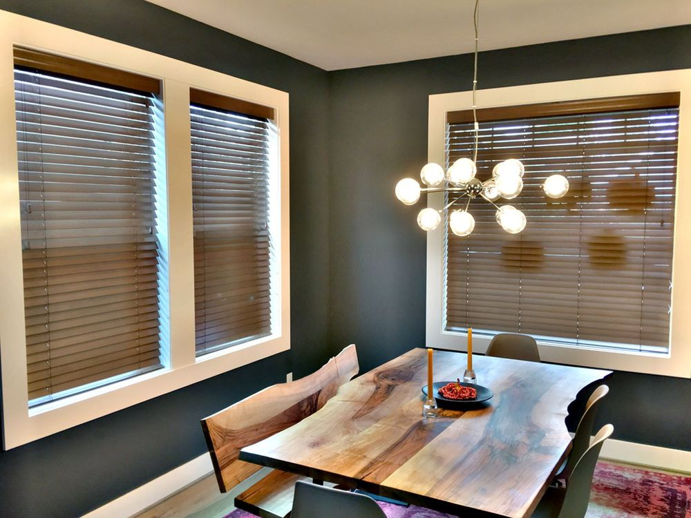 This dining room offers a stylish dining table and chairs set lighted by a charming ceiling light and is surrounded by black walls and a white ceiling.