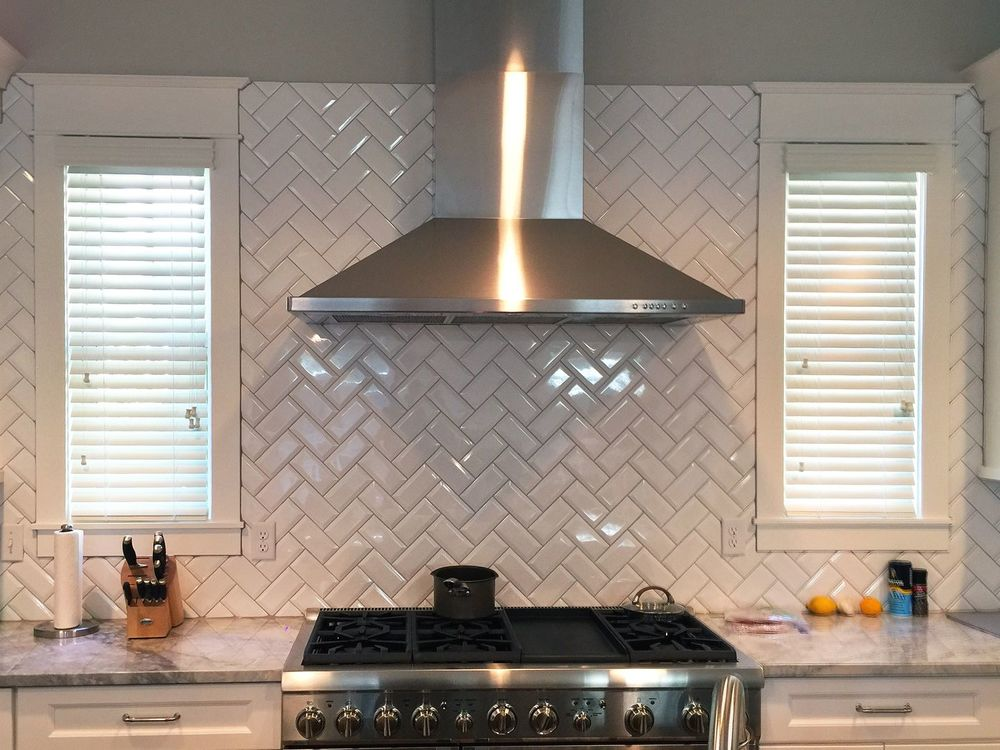 A focused look at this kitchen's stylish tiles backsplash and windows with window blinds.