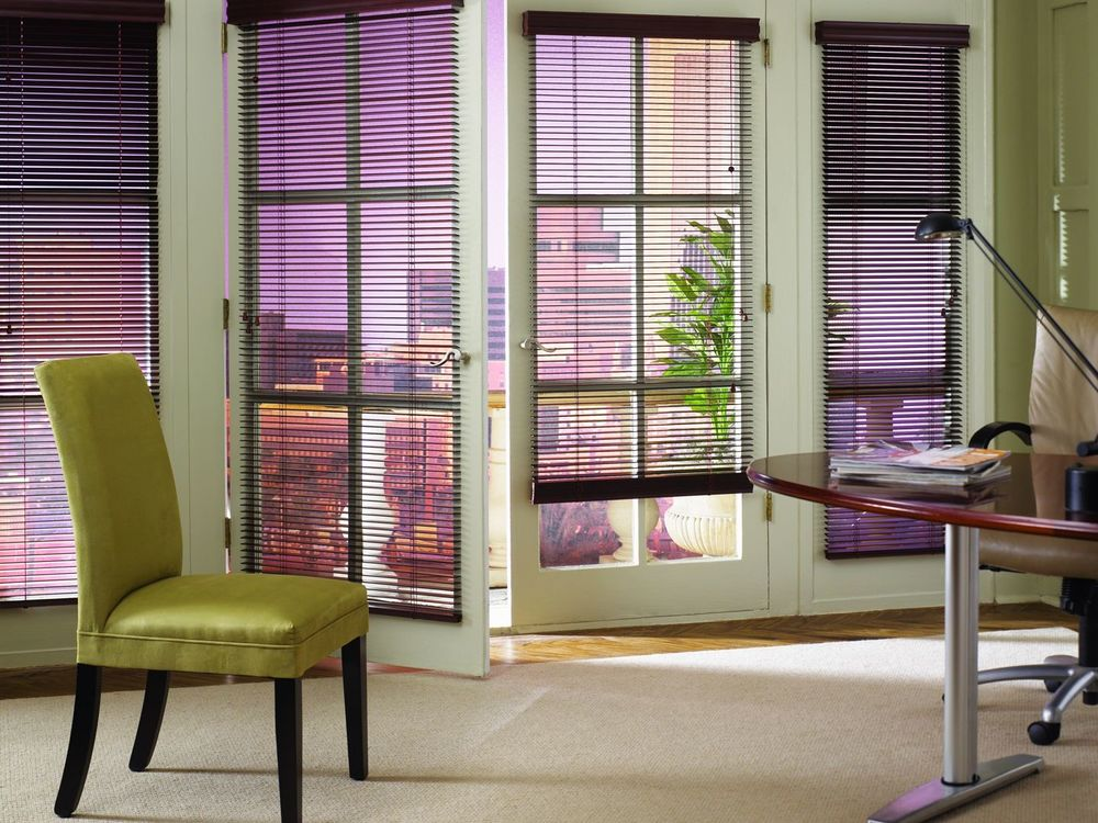 An office area featuring olive green walls and windows with blinds. It offers a classy office desk and chair set. It also has a private balcony area.