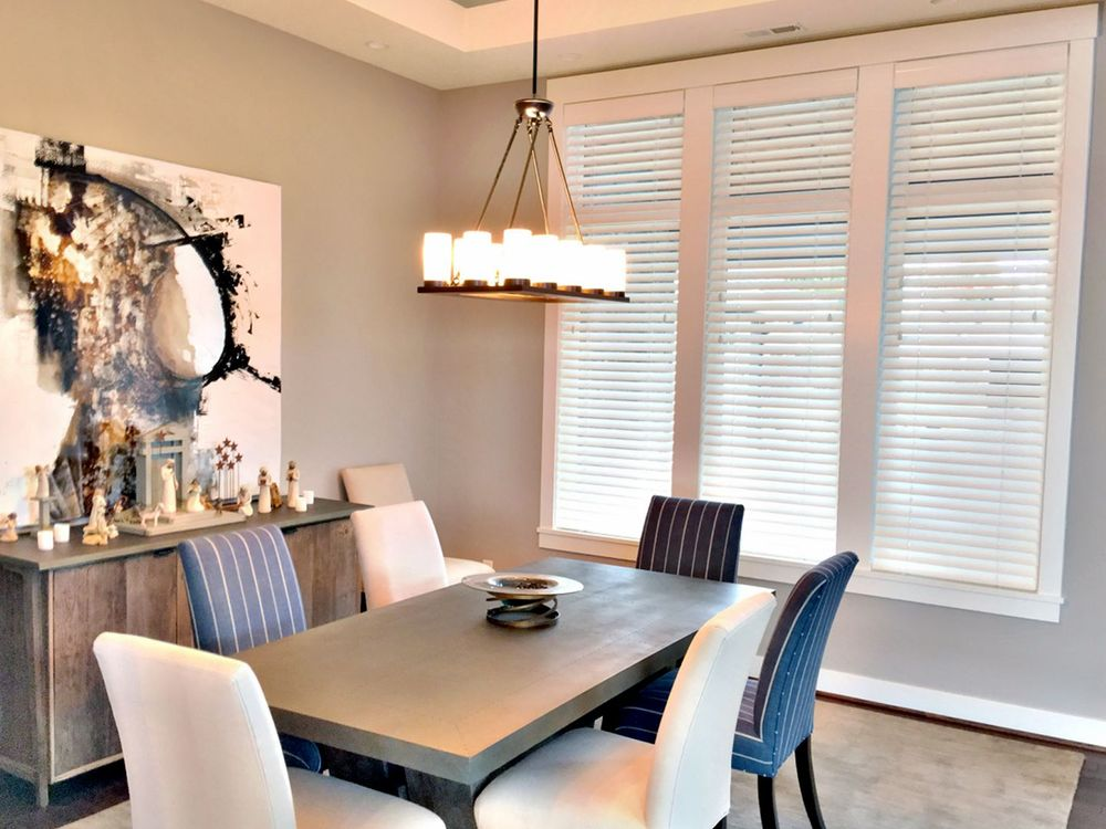 Dining room with a classy set of chairs and a side table with a stylish wall decor nearby. The area features light gray walls and a tray ceiling.