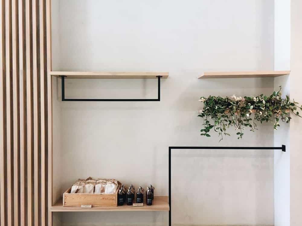 Wood and bracket open shelving mounted on white walls.