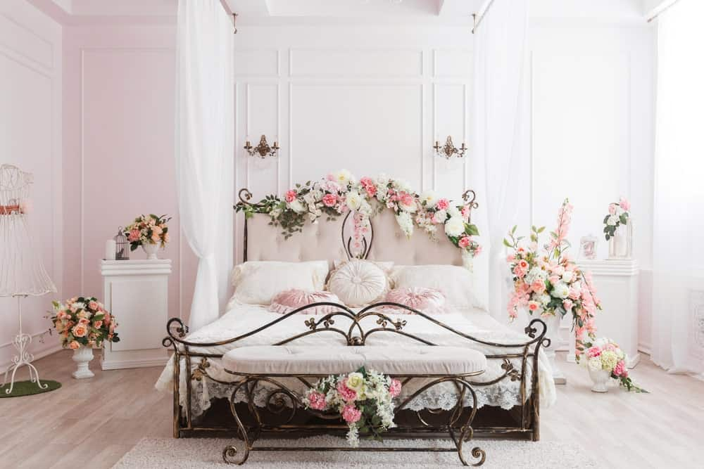 Wrought-iron box-spring bed embellished with flowers.