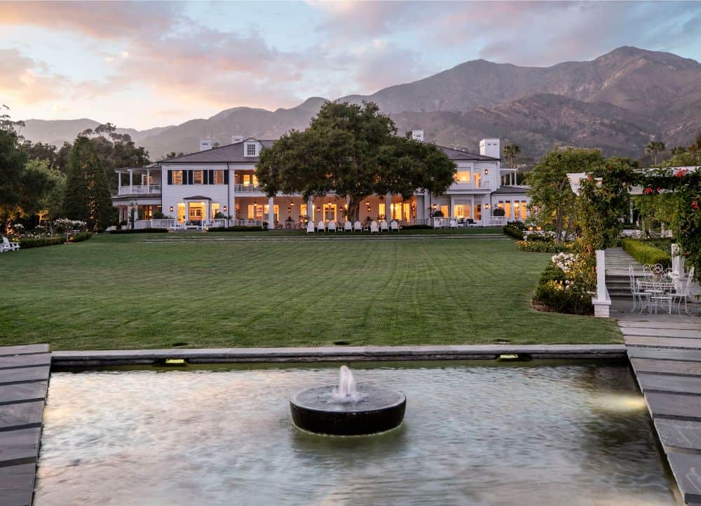 The view of Rob Lowe's mansion's backyard, shot taken from the pool area. This view showcases the well-maintained lawn area and the magnificent house architural design. Images courtesy of Toptenrealestatedeals.com.