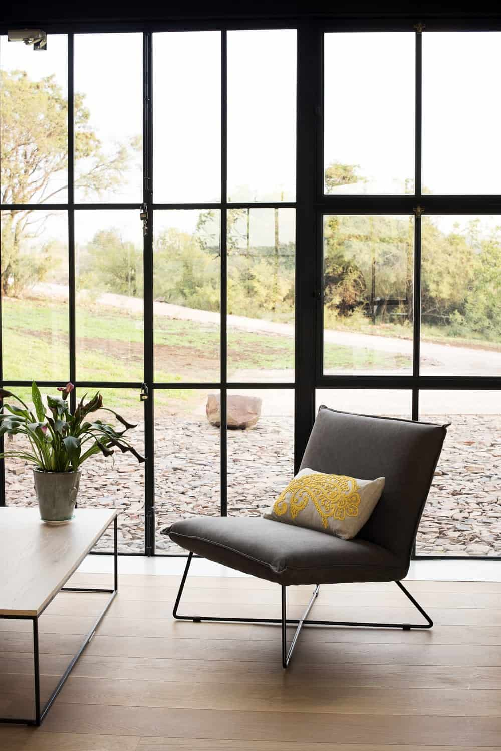 Sitting area overlooking the serene outdoor view in The Conservatory designed by Nadine Engelbrecht.