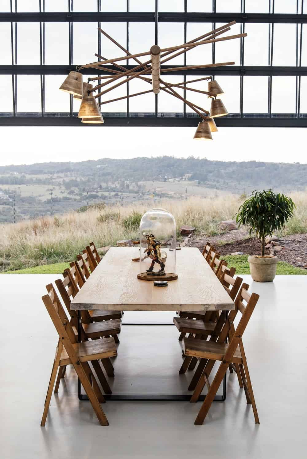Wooden dining set illuminated by contemporary chandelier in The Conservatory designed by Nadine Engelbrecht.