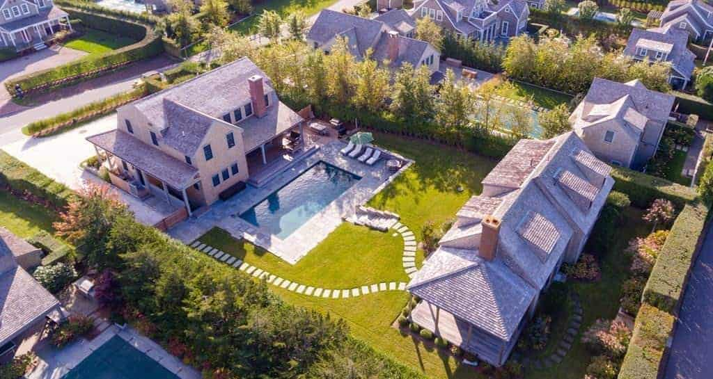 A beautiful property on Nantucket that boasts two homes with colonial architectural style forming a compound. It features wrap around porch and a sparkling pool in the middle.