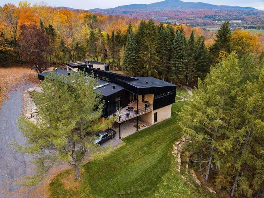 Playful rural house with industrial aesthetic showcasing black flat roofs contrasted by light wood walls and flooring. It is surrounded by towering spruce and pine trees along with a breathtaking mountainside view.