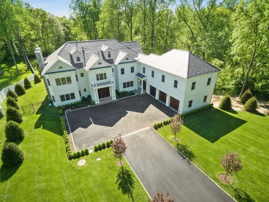 Transitional Georgian style colonial home with modern finishes showcasing pristine white walls and plenty of glazed windows. It includes an expansive lush lawn, manicured shrubs and smaller versions of it surrounding the driveway.