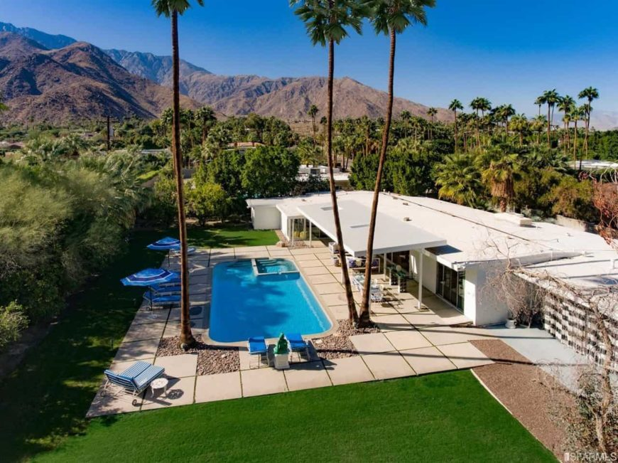 A historical mid-century modern house with a striking backdrop of San Jacinto mountains. It has beautiful landscaping and a tranquil pool with a spa that sits in between tall palm trees.