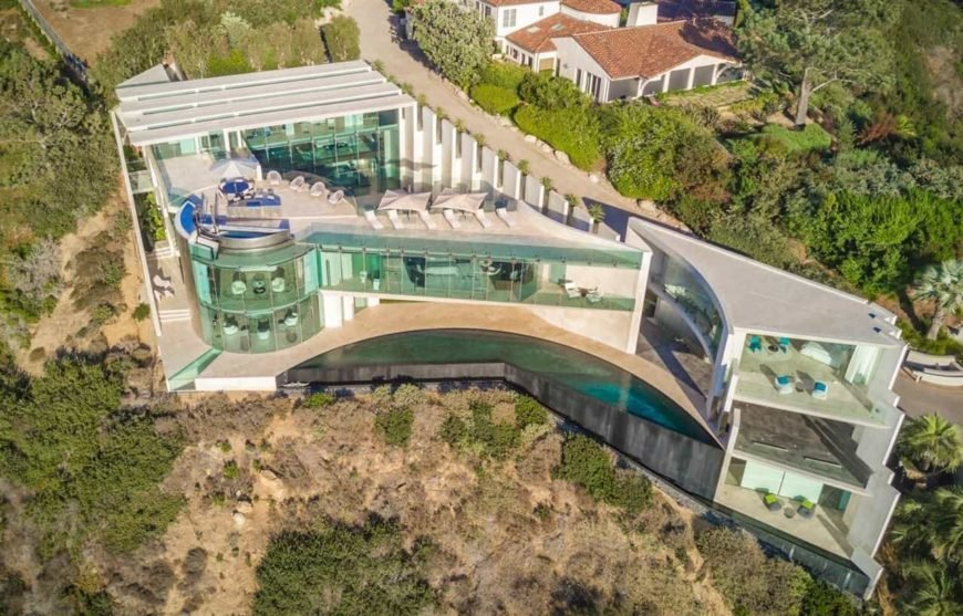 A spectacular razor house boasting a luxurious modern design with its clean lines and tinted full height glazing. It has a magnificent pool, a rooftop entertainment space and cinematic landscaping.