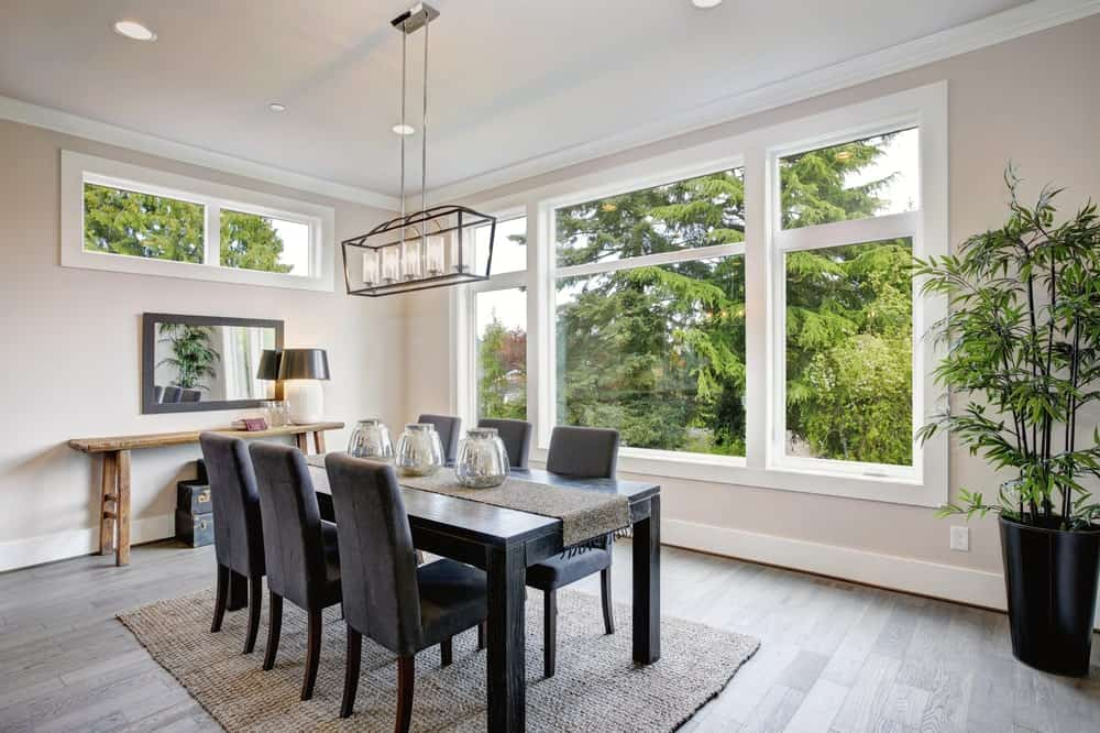 Airy dining room with tall potted plants, white framed windows overlooking the outdoor greenery, beige walls, light hardwood flooring, black dining table surrounded by leather high back chairs, a linear chandelier and rustic console table.