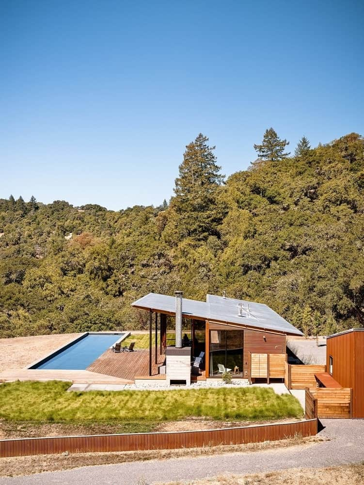 This simple yet charming home has a sloped roof that complements the wooden panels and glass walls of the exterior. These glass windows and outdoor areas are designed to better appreciate the surrounding landscape as well as the beautiful pool at the backyard along with the lawns of fluffy grass.